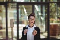 Jovem empresária usando telefone móvel — Fotografia de Stock