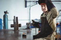 Portrait of welder holding welding machine in workshop — Stock Photo