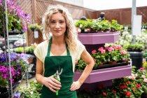 Portrait de femme fleuriste tenant des cisailles en jardinerie — Photo de stock