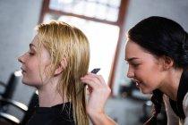 Parrucchiere pettinando i capelli del cliente nel salone — Foto stock