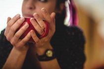 Immagine ritagliata di donna che prende il caffè a casa — Foto stock