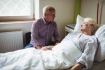Senior man consoling senior woman in hospital ward — Stock Photo