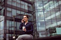 Giovane donna che parla al telefono cellulare contro edificio moderno — Foto stock