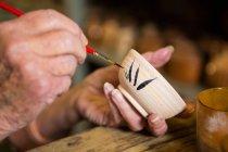 Обрезанное изображение гончарной живописи на чаше в керамической мастерской — стоковое фото