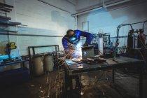 Чоловічий зварювальник, працюючи на шматок металу в майстерні — стокове фото