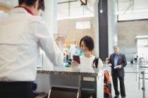 Atendente de check-in da companhia aérea que entrega passaporte ao passageiro no balcão de check-in do aeroporto — Fotografia de Stock