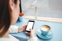 Cropped image de messagerie sur téléphone mobile dans la cafétéria de texte femme — Photo de stock
