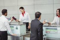 Сотрудники авиакомпании при регистрации вручают паспорт пассажирам на стойке регистрации в аэропорту — стоковое фото