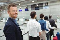 Passagers en attente à un comptoir d'enregistrement avec bagages à l'intérieur du terminal de l'aéroport — Photo de stock