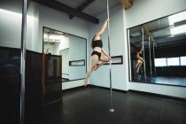 Pole dancer practicing pole dance in fitness studio — Stock Photo