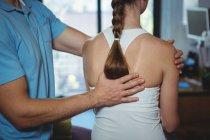 Image recadrée d'un physiothérapeute massant le dos d'une patiente en clinique — Photo de stock