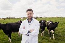 Портрет умного ветеринара, стоящего против коров на поле — стоковое фото