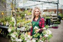 Ritratto di fiorista donna in piedi nel centro del giardino — Foto stock