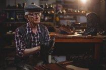 Старший сапожник чинит обувь в мастерской — стоковое фото