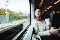 Belle femme assise par la fenêtre en train — Photo de stock