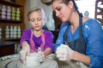 Жіночий Поттер, допомагаючи дівчина в гончарної майстерні — стокове фото