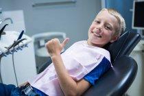 Jeune patient souriant assis sur la chaise du dentiste et montrant ses pouces à la clinique — Photo de stock