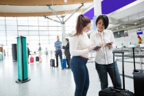 Two women checking their passports in airport terminal — Stock Photo