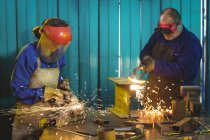 Male and female welders working together in workshop — Stock Photo