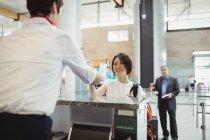 Flugbegleiter reicht Passagieren am Flughafen-Check-in-Schalter den Reisepass — Stockfoto