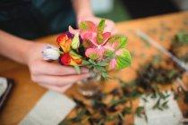 Primo piano del fiorista femminile organizzazione dei fiori in una bottiglia al suo negozio di fiori — Foto stock