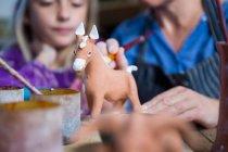 Закри жіночий Поттер допомога дівчина в живопису гончарної майстерні — стокове фото