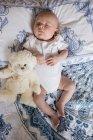 Vue de dessus de bébé dormir sur le lit avec ours en peluche dans la chambre — Photo de stock