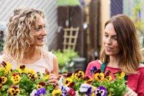 Femme fleuriste parlant des plantes en jardinerie pour femme — Photo de stock