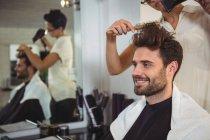 Улыбающийся человек сушит волосы феном в салоне — стоковое фото