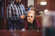 Femme se faire couper les cheveux avec tondeuse dans le salon de coiffure — Photo de stock
