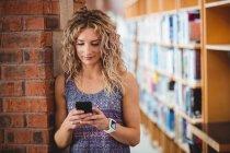 Красивая женщина с помощью мобильного телефона в библиотеке — стоковое фото