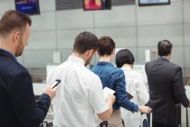 Passengers waiting in queue at a check-in counter with luggage inside the airport terminal — Stock Photo