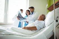 Médicos que interactúan por rayos X con el paciente en el hospital - foto de stock