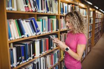 Frau benutzt Handy in Bibliothek — Stockfoto
