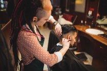 Людина стає його волосся з обробкою з бритвою в перукарні — стокове фото