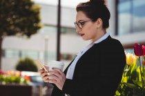 Giovane donna d'affari in possesso di telefono cellulare e tazza di caffè usa e getta — Foto stock