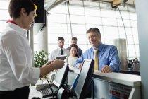 Companhia aérea entrada atendente entregando o cartão de embarque aos passageiros no balcão de check-in Aeroporto — Fotografia de Stock