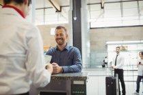 Flugbegleiter kontrollieren am Flughafen-Check-in-Schalter den Reisepass des Passagiers — Stockfoto