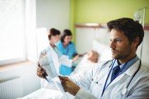 Arzt überprüft Röntgenbericht im Krankenhaus — Stockfoto