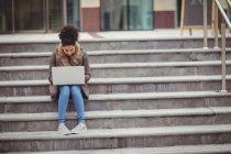 Volle Länge der Frau mit Laptop, während sie auf Stufen sitzt — Stockfoto