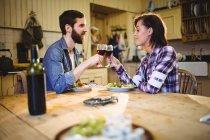 Pareja tomando vino y cenando en casa - foto de stock