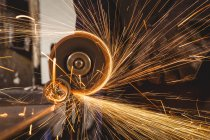 Cropped image of welder cutting metal with electric tool in workshop — Stock Photo