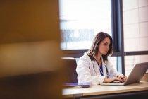 Medico femminile che utilizza il computer portatile alla scrivania in ospedale — Foto stock