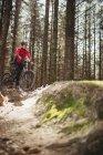 Мужчина горный велосипедист с велосипедом среди деревьев в лесу — стоковое фото