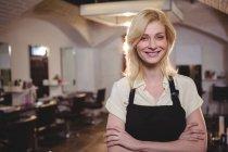 Портрет жіноче перукар, стоячи з руки перетнув в салон — стокове фото