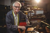 Sorridente calzolaio anziano martellare su una scarpa in officina — Foto stock