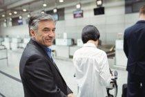 Empresario esperando en cola en un mostrador de facturación con equipaje en la terminal del aeropuerto - foto de stock