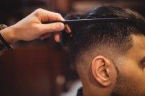 Homem recebendo seu cabelo aparado na barbearia — Fotografia de Stock