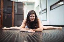 Ritratto di pole dancer disteso sul pavimento in sala fitness — Foto stock