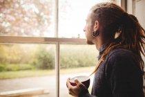 Seitenansicht des Hipsters, der eine Kaffeetasse hält, während er zu Hause durch das Fenster schaut — Stockfoto